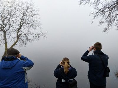 three-people-looking-out-over-a-loch-in-foggy-conditions