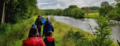 group-walking-along-the-banks-of-River-Teith-in-Callander-during-the-Callander-SummerFest-festival-in-July-2019