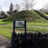 interpretation-panel-in-front-of-grassy-mound-Hill-of-St-Kessog