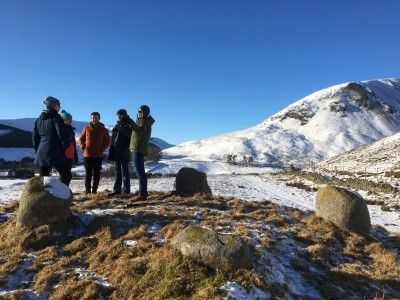 five-people-talking-in-a-group-with-snowy-hills-in-the-background