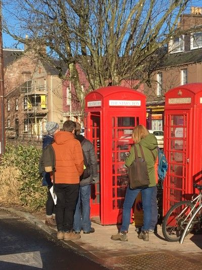 people-standing-outside-an-old-fashioned-red-telephone-box