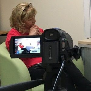 Camera with screen flipped open, showing woman being interviewed
