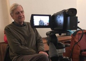 Camera and flip out screen showing man being interviewed