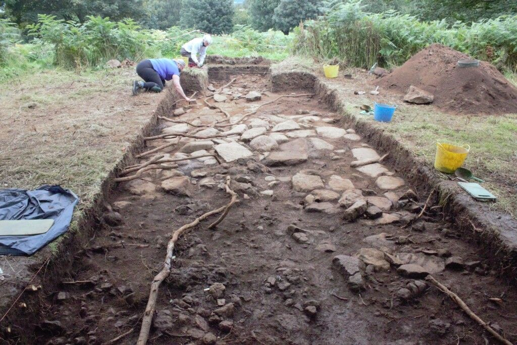The trench at full size with the membrane lifted. This revealed the flat paving stones of either the longhouse floor or the courtyard. The curve of the rocks visible revealed which direction the longhouse curved.
