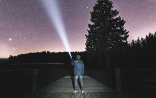 photo of a man shining a torch into a starry sky