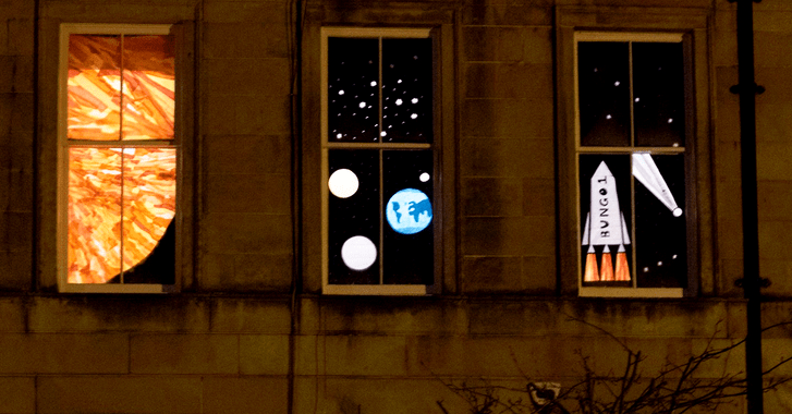 Three windows in a home decorated showing a space view with planets, stars and a rocket.