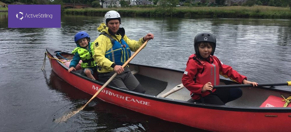 a-man-with-two-children-in-a-canoe-on-a-river